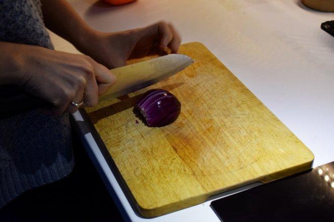 Cortando cebolla morada para receta tradicional de lentejas con Caldo aneto de puchero