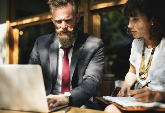 Imagen de un jefe y una empleada ante un portatil en pose colaborativa, para el post la conciliación no existe son los padres