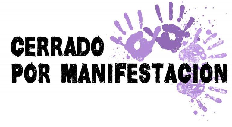 Cartel blanco con manos pintadas en violeta y el texto escrito similar a mano que reza Cerrado por manifestación, por la manifestación de la mujer.