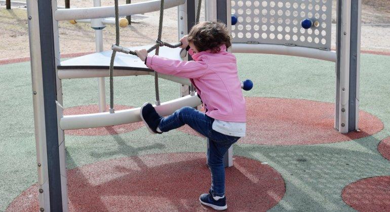 """Hija, quiero que seas una mujer libre. Niña con chaqueta rosa y ropa """"de niño"""" escalando unos columpios"""