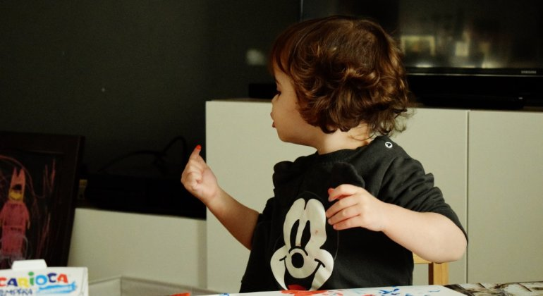 un dia cualquiera adoslescente, niña de dos años mirando hacia atrás mientras pinta con temperas