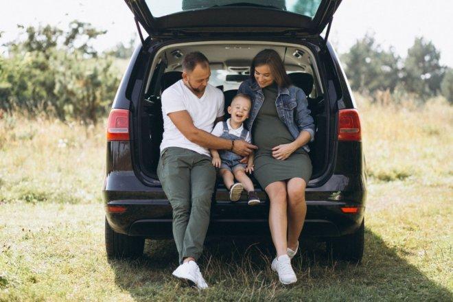 Familia feliz sentada en el maletero del coche para el post a contramarcha es más seguro