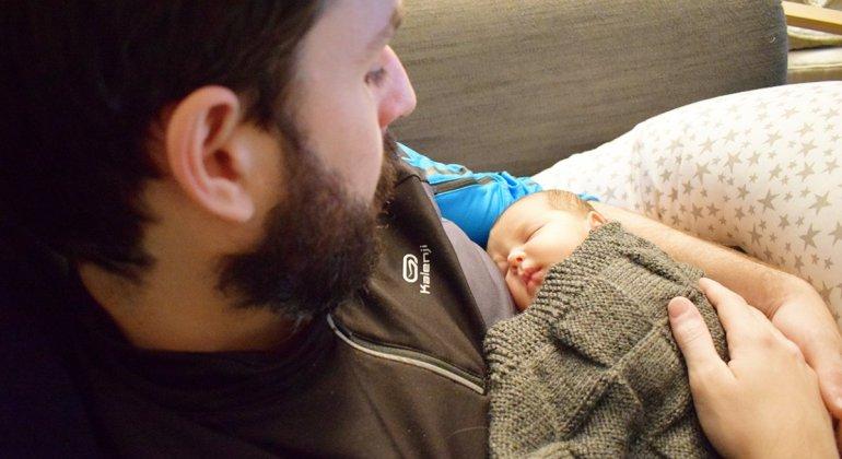 Padre que ha dormido a su bebé, como parte de su papel activo en la crianza y la lactancia materna