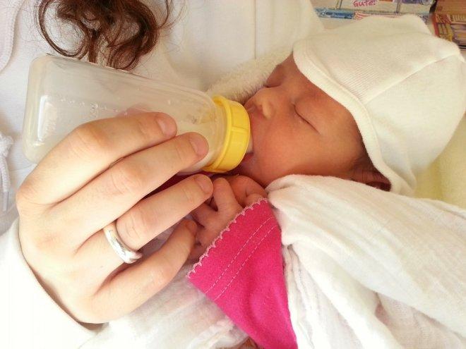 Mamá dando un biberón  aun recien nacido, entorpece la lactancia materna
