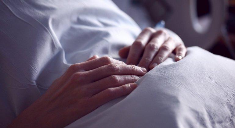 Mujer vestida de hospital tocándose la barriga, a punto de ponerse el DIU como método anticonceptivo femenino