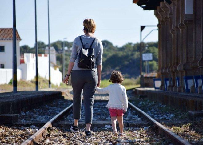 madre e hija caminando por unas vias abandonadas en portugal