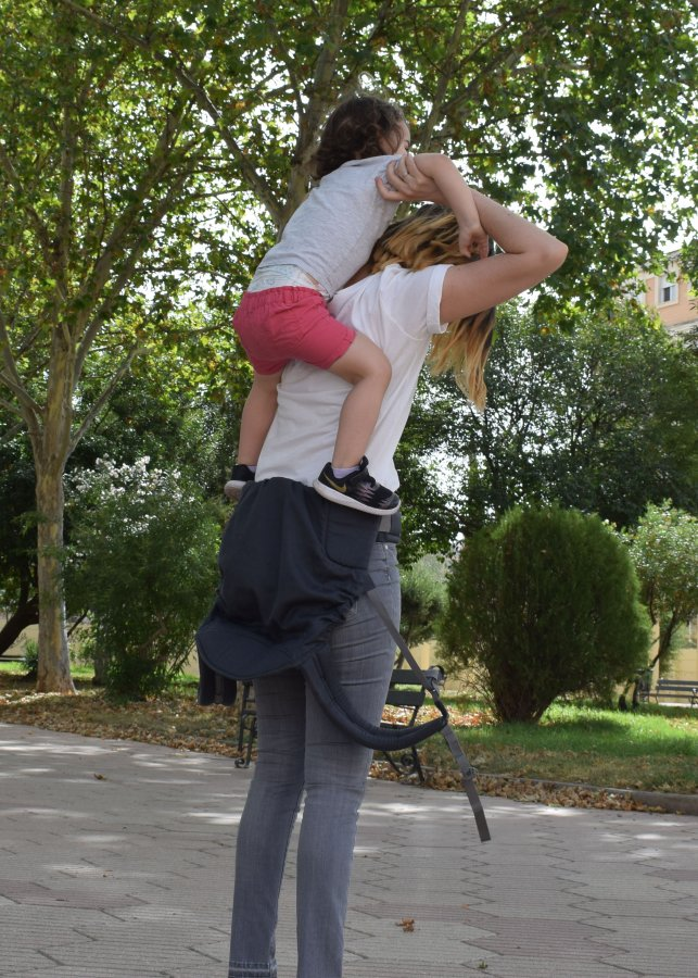 mamá subiendo a su niña de 2 años a la espalda en una mochila evolutiva tipo toddler