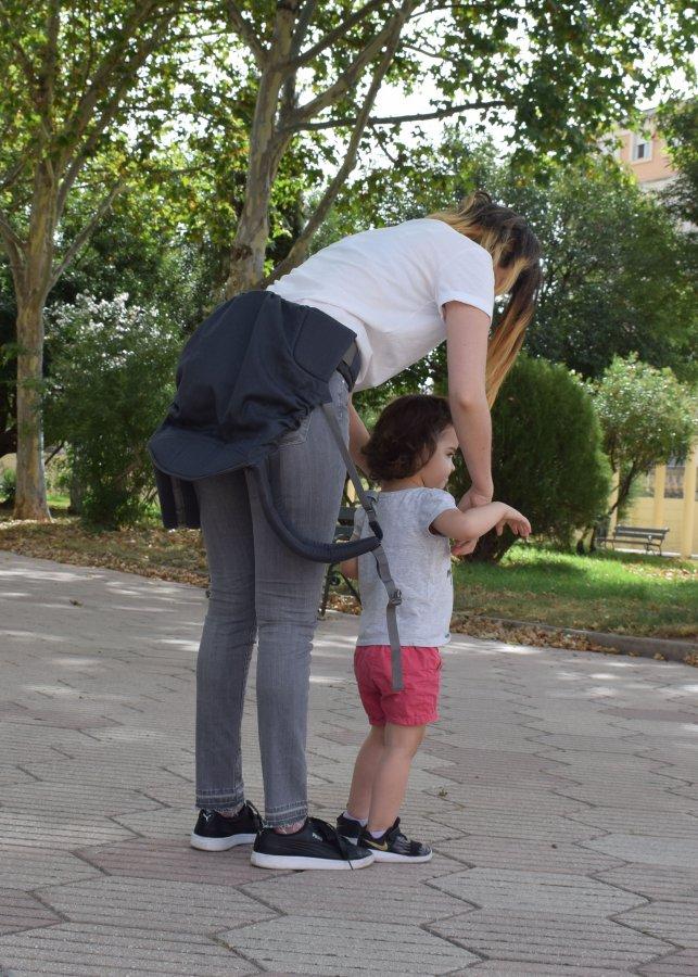 mamá subiendo a su hija a una mochila de porteo ergonómica