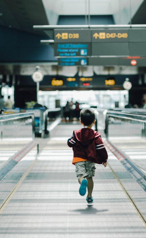 Niño corriendo por el aeropuerto, viajar y volar con niños