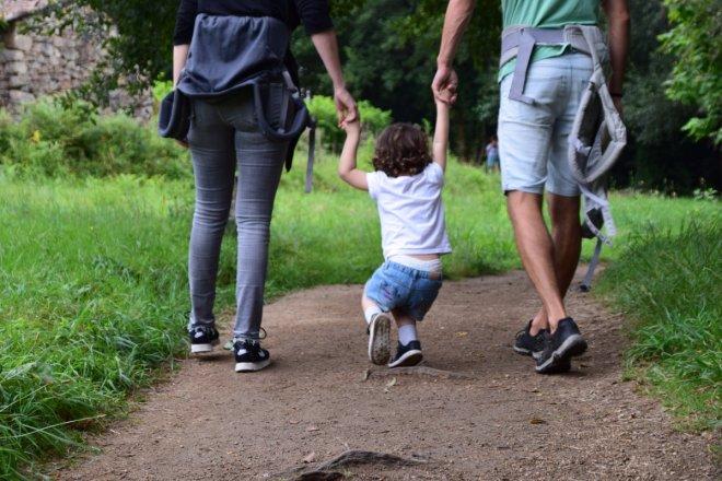 Familia que tiene tiempo de jugar con sus hijos y disfrutar de la naturaleza por ahorrar y permitirse una excedencia siendo padres.