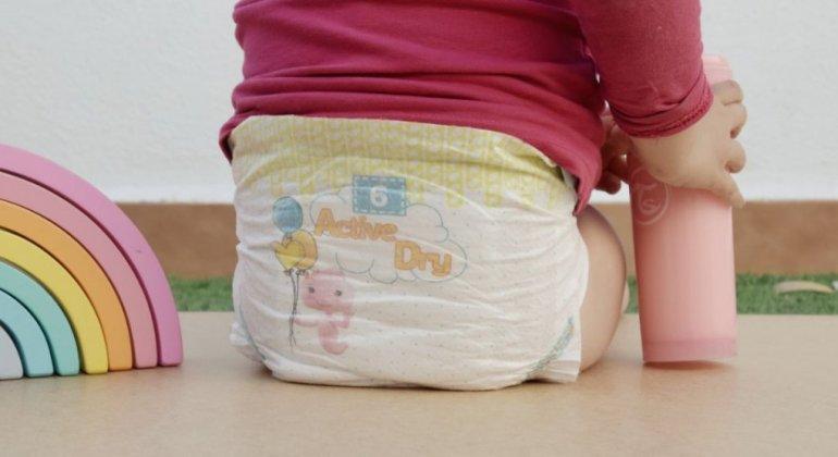 niña con pañal, sentada al lado de un arcoiris, operación dejar el pañal