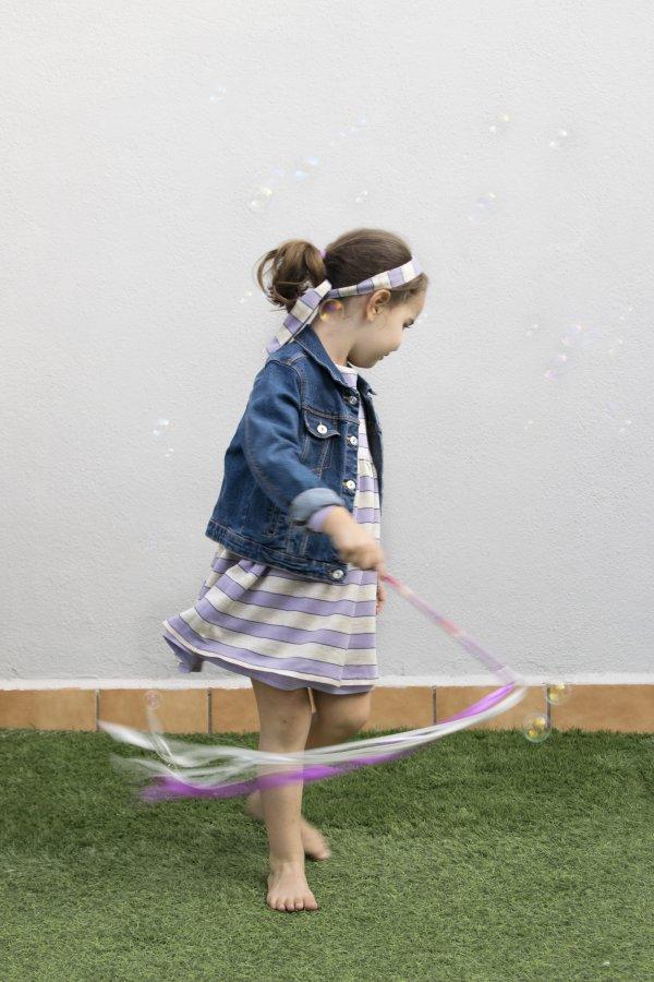 Niña con vestido lila y beige de la marca Giro ropa reversible, con chaqueta vaquera y diadema a juego, jugando a ser bailarina