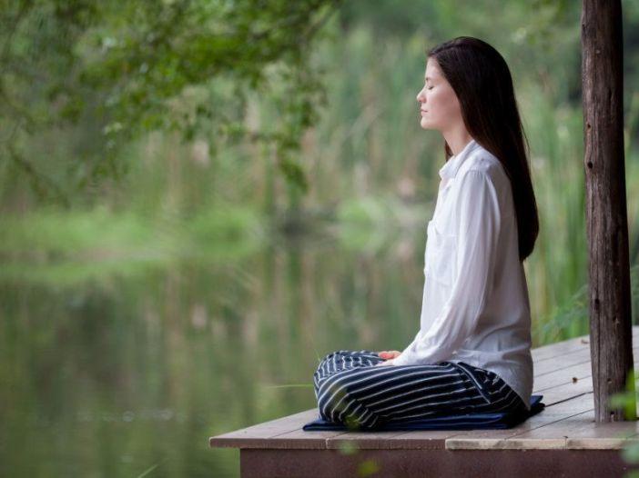 Fotografía de una mujer meditando junto a un lago o estanque j