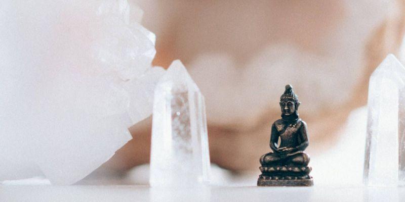 Fotografía de una escultura de Buda junto a unos cristales de cuarzo