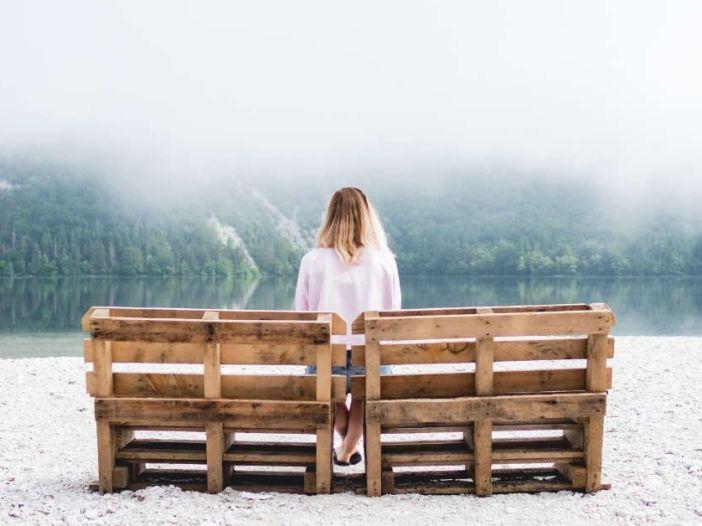 Mente en blanco. Fotografía de una mujer de espaldas sentada en un banco en un entorno con niebla