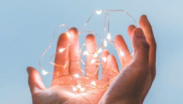 Manos en gesto de gratitud sosteniendo unas luces