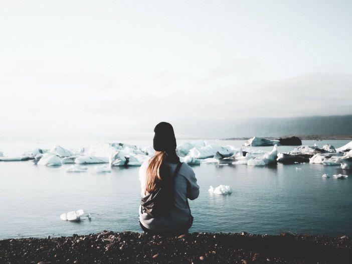 Chica de espaldas observa un mar con pedazos de hielo flotando