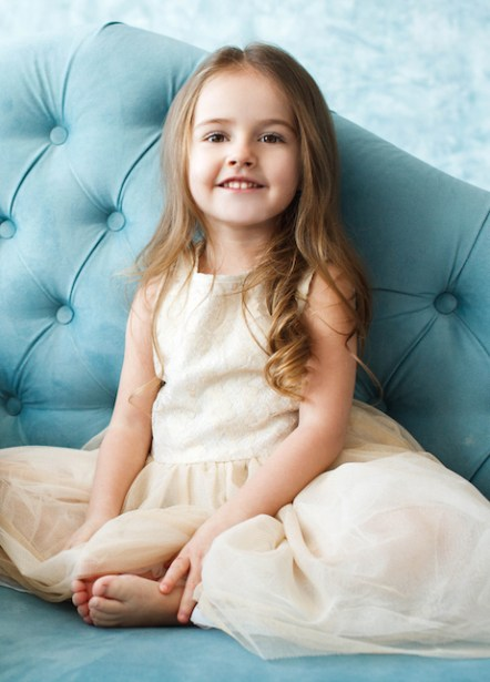 Gorgeous little girl with dark blonde hair lies on blue couch