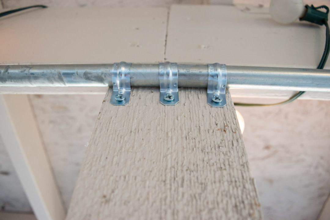 Closeup of backyard patio conduit pipe curtain rod