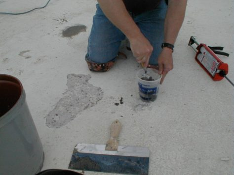 Mixing 10 Minute Concrete Mender with sand in a bucket prior to repairing a spall in the concrete pool floor.