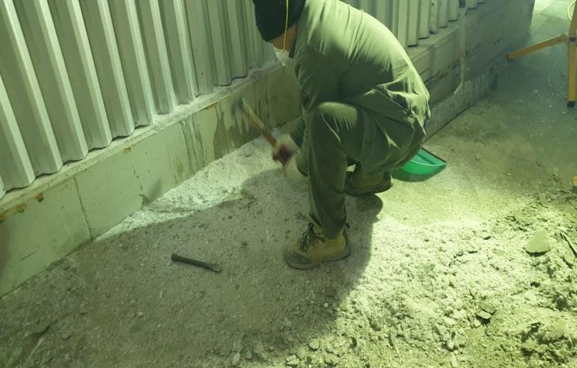Freezer floor being prepared for coating with Roadware Freezer Coating by grinding the surface flat with metal grinding pads.