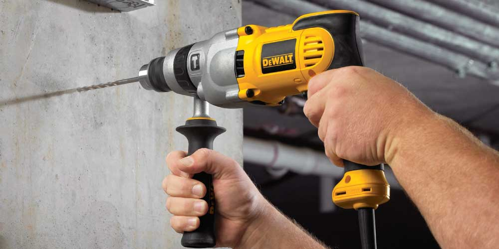 The Dewalt DWD520 Hammer Drill, drilling into a concrete wall.