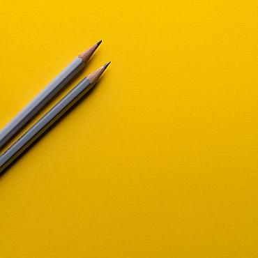 2 pencils on yellow background by Joanna Kosinska