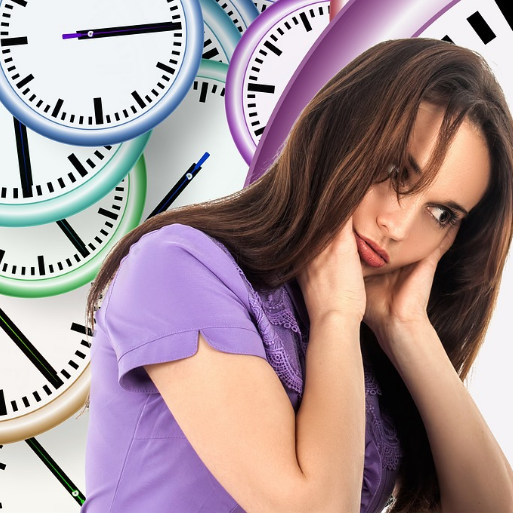 Woman head in hands wearing a purple t-shirt sitting in front of many clocks of pastel colours.