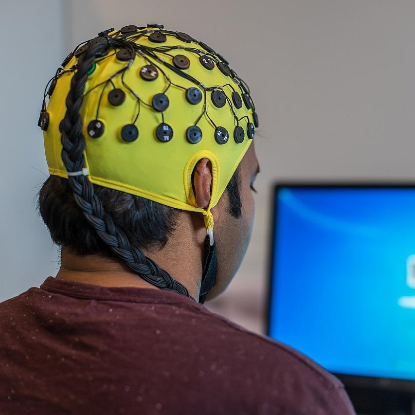 Man facing a computer with yellow EEG skullcap on