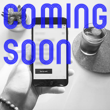 Hand holding smartphone with lines of blurred text over a white table with drink on a coaster to right and small plant to left with COMING SOON text
