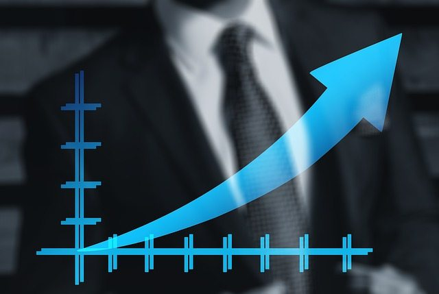 Man in suit with graph showing increasing stats
