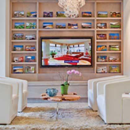 Sitting area and wall unit with TV and Sotheby's marketing documents.