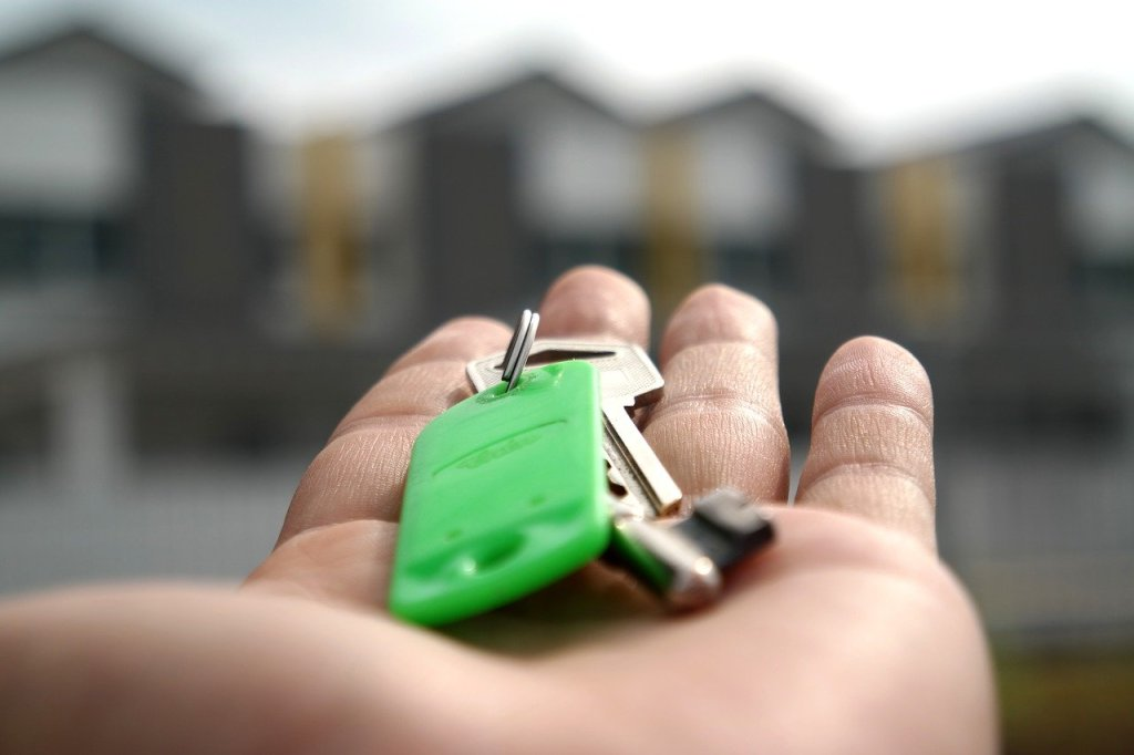 Hand with a set of house keys on a green keychain.