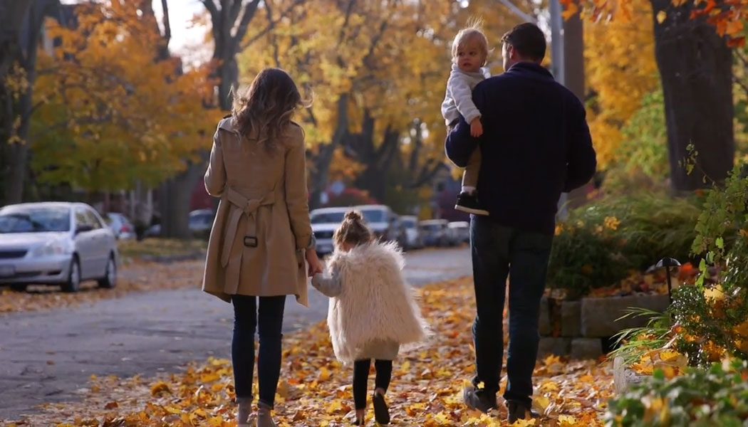 Family on sidewalk with fall leaves on the ground.