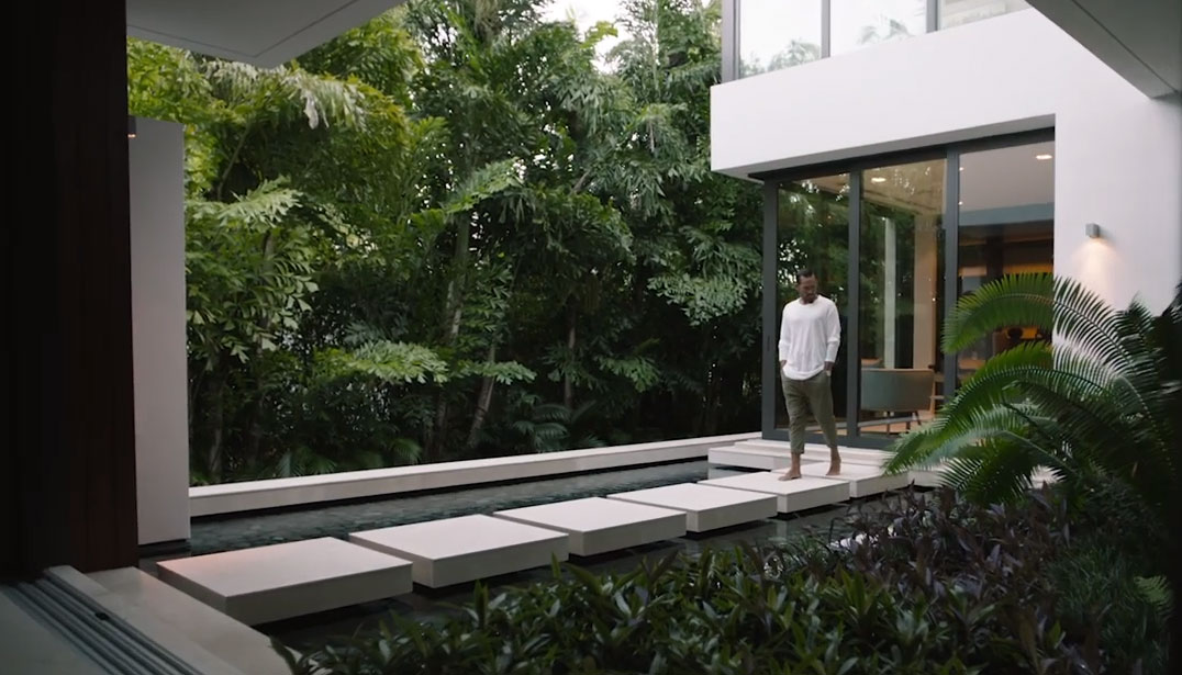 Man walking across modern outdoor path at a private home.