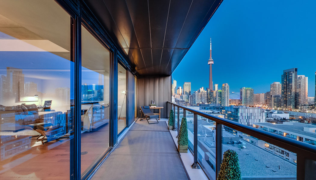 Condo balcony with night time view of the city and the CN Tower in Toronto.