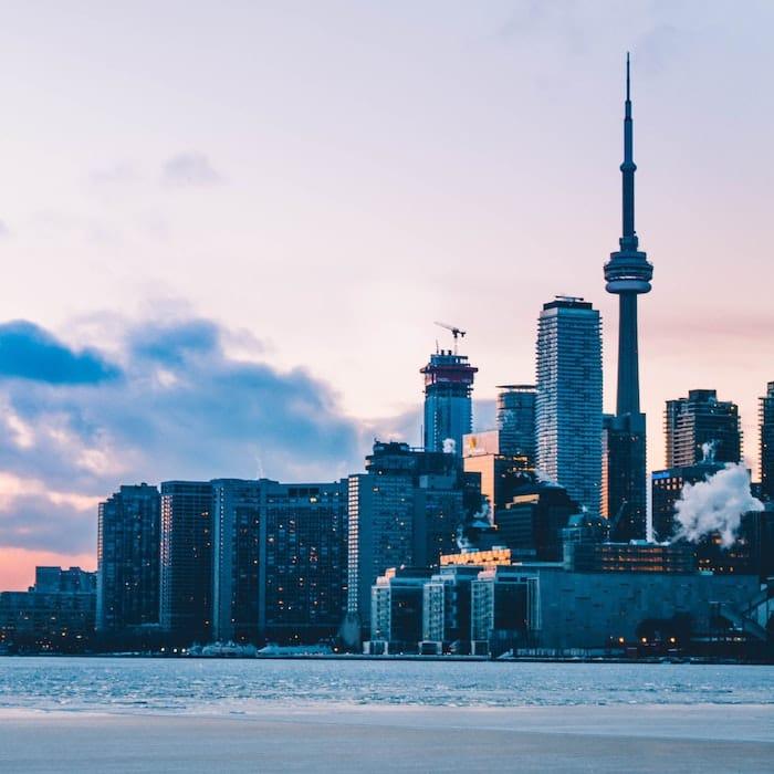 Toronto skyline from island beach at dusk.