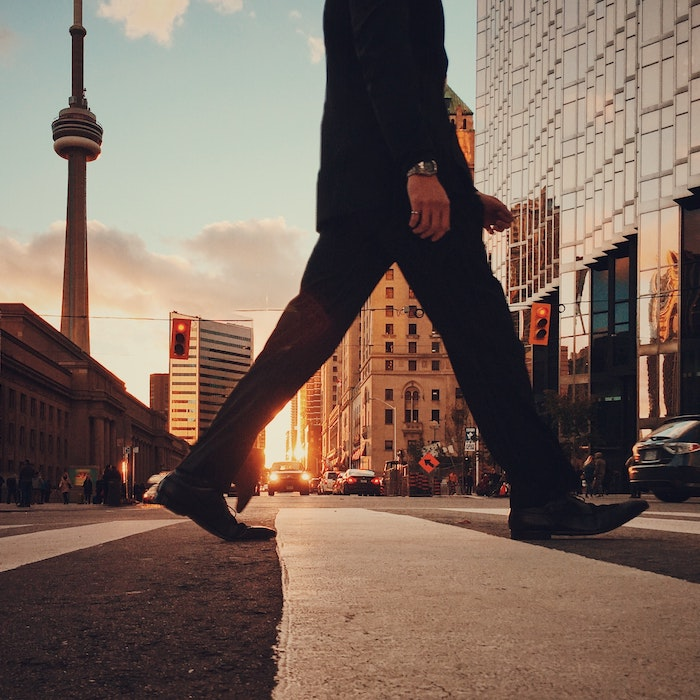 A man walking in Toronto with the CN Tower in the background.