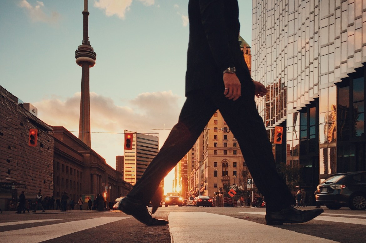 A man walking in Toronto with the CN Tower in the background. Photo by Arturo Castaneyra