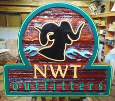 Custom made artist painted sandblasted cedar sign for NWT out fitters.Condor Signs BC
