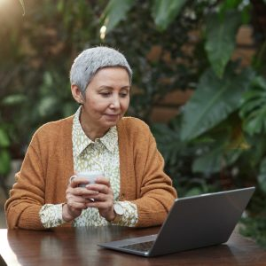 Woman in her sixties looking at her laptop holding cup of coffee - seniors technology