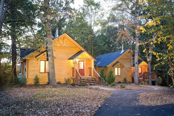 log resort cabin at dusk in woods