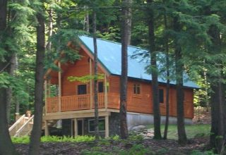log cabin in woods with stream