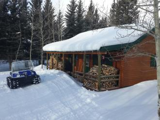Trout Run Conestoga log cabin kit in snow with snow mobile