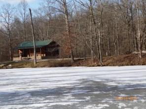 Bear Creek log cabin across frozen lake