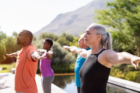 older men and women practicing Yoga breathing exercises outdoors