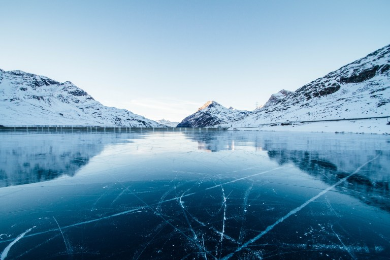 View of an ice covered lake with mountains in background