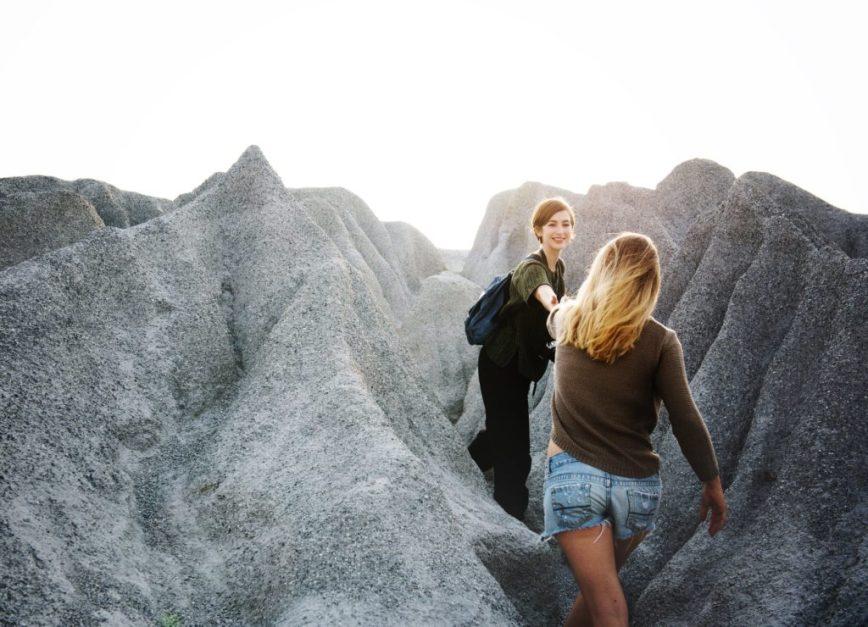 Woman helping person through mountain trail
