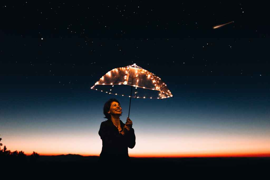 Woman with light up umbrella smiling at night time