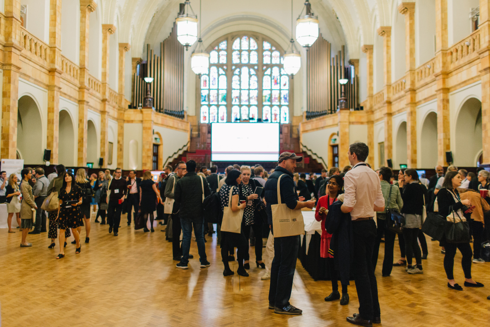 Delegates networking in the Great Hall in front of a screen